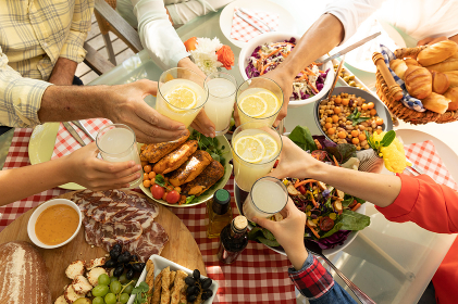 Overhead view of the hands of a multi-generation Caucasian family sitting outside at a dinner table set for a meal, raising glasses together and making a toast across the table. Family enjoying time at home, lifestyle concept