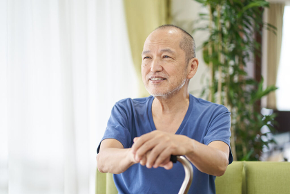 杖をつき笑顔で座る高齢者