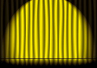 スポットライトの当たった黄色のステージカーテンと反射している舞台の床