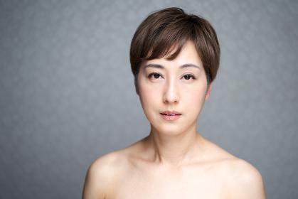 カメラ目線で真顔で見つめる中年の日本人女性