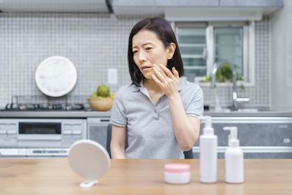 不安な表情で肌の状態を確かめる中年女性