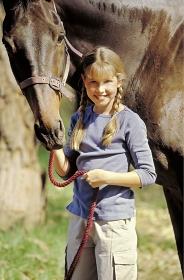 Portrait, Maedchen, 12 Jahre, mit langen blonden Zoepfen mit ihrem gehalfterten Pferd