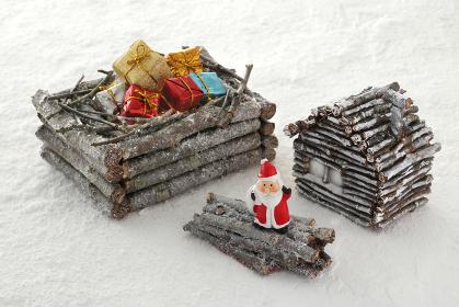 雪をかぶった木で出来た家や箱のあるクリスマスのイメージ