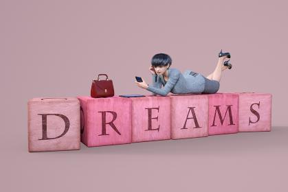 DREAMSと書かれたボックスの上に寝転ぶショートヘアでスーツを着た女性社員がスマートフォンを見る