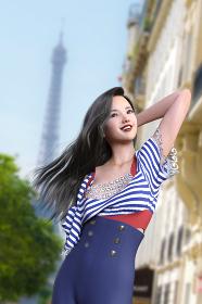マリン風の青いボーダー柄の服を着たロングの黒髪の綺麗な女性が高い建造物の前で髪をかきあげている