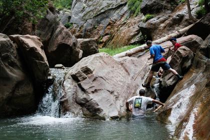 アメリカのザイオン国立公園にて岩壁に囲まれた川の中を歩きトレッキングする男性