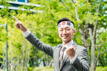 「必勝」の鉢巻を巻いて手を上げる男性