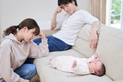 泣き止まない赤ちゃんに疲れるアジア人の両親