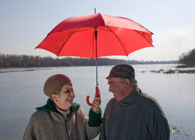Senior couple by river sharing umbrella