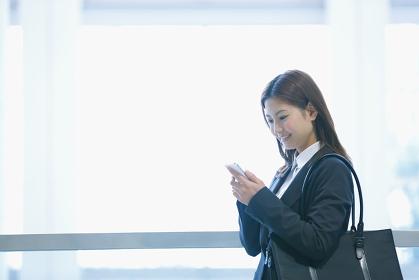 携帯を見るビジネスウーマン