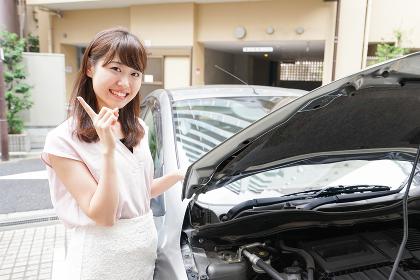 車のメンテナンスをする女性
