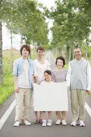 メッセージボードを持ち微笑む3世代家族