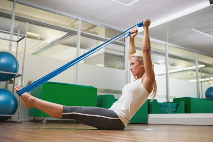 Side view of woman using resistance band in fitness studio