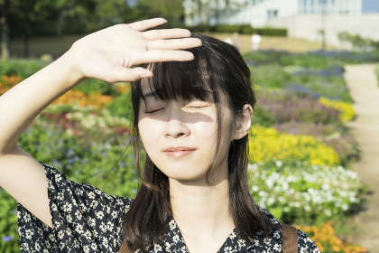 まぶしい太陽光を手でさえぎるアジア人の若い女性