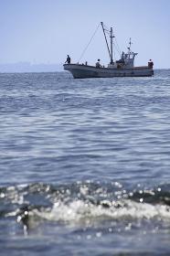 岬の沖で釣り糸を垂らす釣り船と浅瀬の波