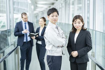 作業服姿とスーツ姿のビジネスチーム男女