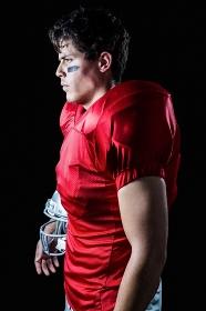 Side view of determined sportsman holding helmet