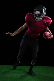 American football player leaning sideways with ball in one of his hand