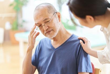 頭痛を起こす高齢者と心配する家族