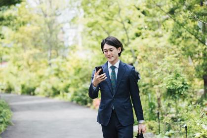 通勤中にスマートフォンを使用するビジネスマン・IoTイメージ