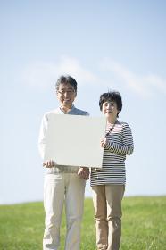 草原でメッセージボードを持つシニア夫婦