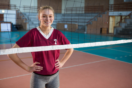 Smiling female volleyball player standing with hand on hips in the court