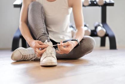 トレーニングジムで靴紐を結ぶアジア人女性