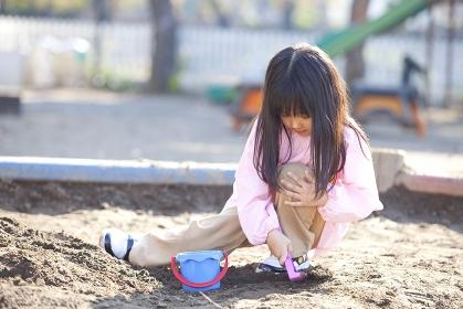 砂場で遊ぶ幼稚園女児