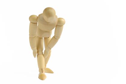 膝が痛いポーズをした前向きの木製のモデル人形