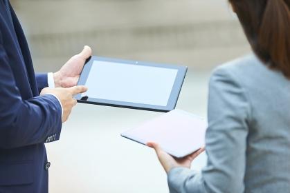 スマートフォンを指さすビジネスマンとビジネスウーマン