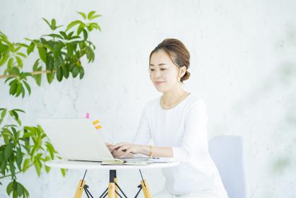 明るい部屋でノートパソコンを操作する女性