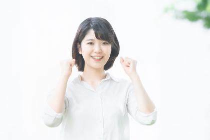 笑顔でガッツポーズをする若い女性