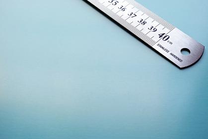 青い紙の右上に斜めに置いたステンレスの物差し