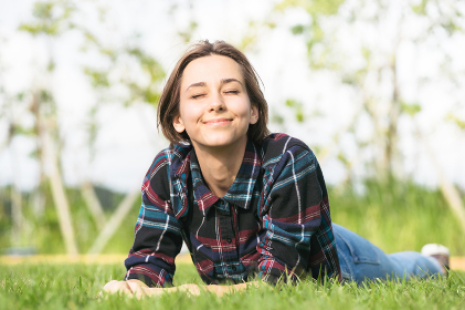 芝生に寝そべる若い笑顔の女性