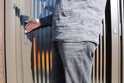 ジーパンを着た男性が家の玄関から出てくる