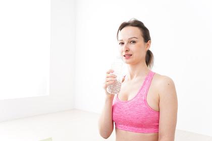 スポーツウェアを着て水分補給をする外国人の女性