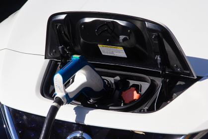 充電ステーションで充電する電気自動車の給電口と充電ホース