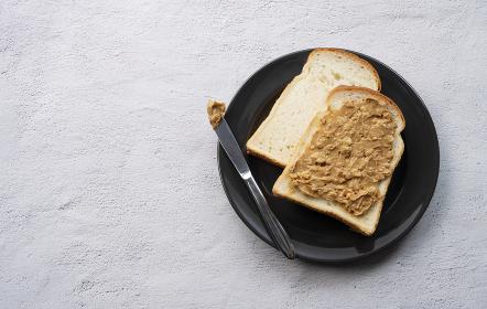 石の背景にピーナッツバターを塗った食パン