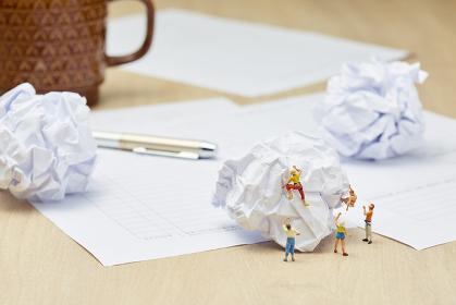 丸められた紙とフィギュア人形