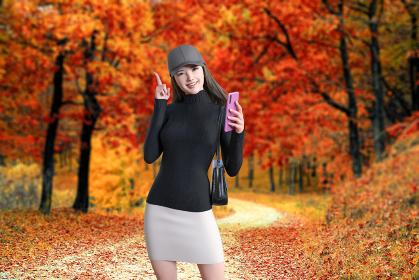 真っ赤に紅葉した森林の中を散歩する帽子をかぶった笑顔の女性がピンクのスマートフォンを片手にポーズする