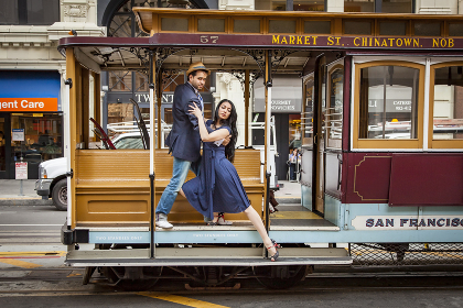 millenial couple dancing on a cable car in San Francisco.