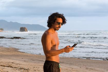 Man using smartphone on beach at sunset