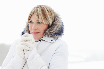 Young woman in fluffy hood in the snow