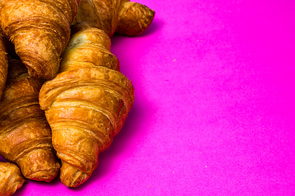 French breakfast concept. Close up of delicious, fresh croissants isolated on pink board.