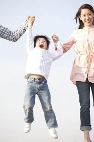 両親に手を引かれてジャンプする男の子