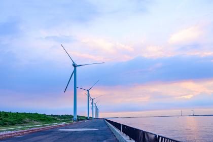夕暮れの空にそびえたつ風力発電機