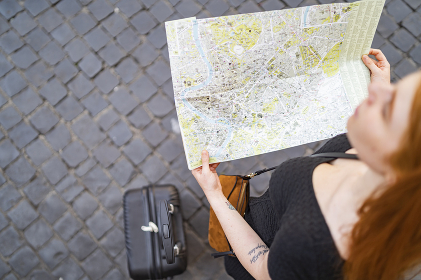 red hair woman with trolley hold a city map on sanpietrini