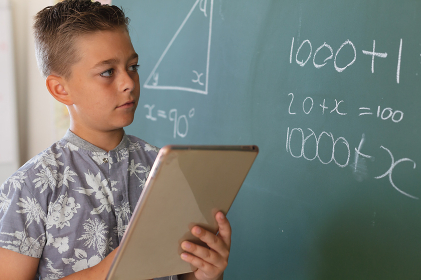 Caucasian boy standing at chalkboard in classroom and using tablet during maths lesson. childhood and education at elementary school.