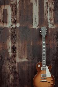 古いレトロな倉庫の壁に並べたエレキギターとアンプ