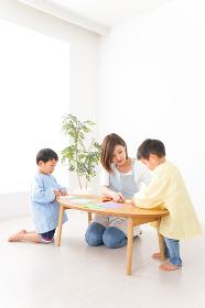 幼稚園で折り紙をする子どもと先生